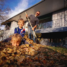 Man raking leaves with children in leaf pile